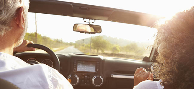 Rearview Of Mature Couple Driving Along Country Road In Open Top Car