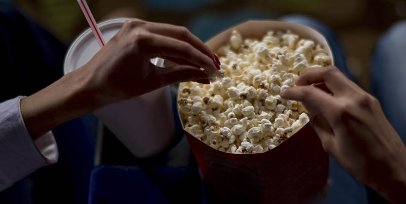 Unrecognisable people eating popcorn at the movies