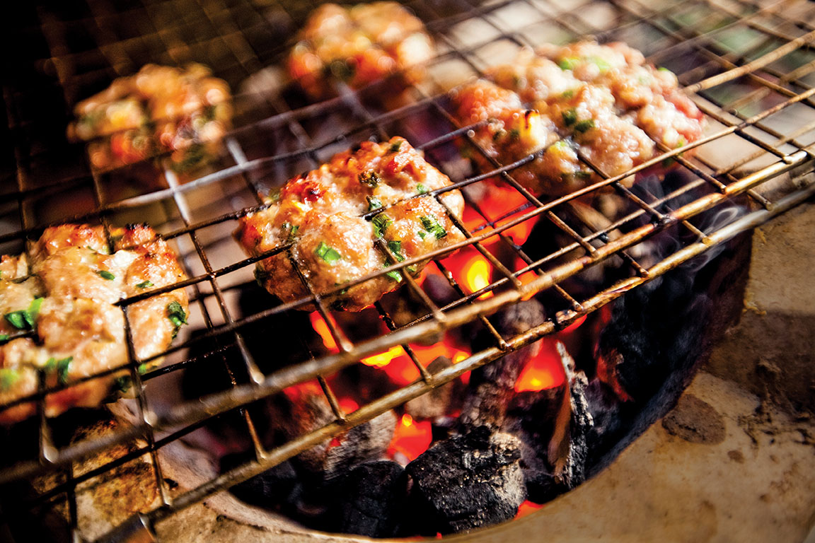 Small herbed pork patties, the base for bun cha, a popular street food, cook over an open flame on the street in Hanoi, Vietnam, Asia.