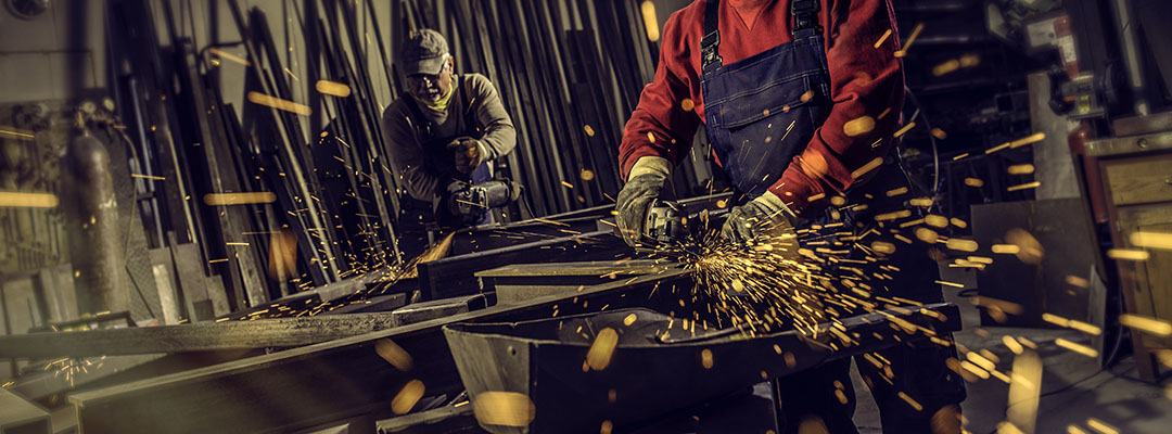 Metal workers cutting a metal objects with circular saws in small workshop.