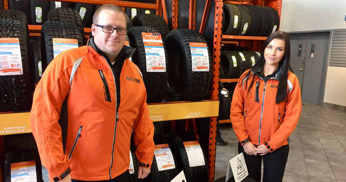 Amber and Geoff, Kal Tire spokespeople. standing in front of a rack of winter tires