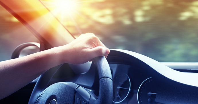 Hand resting on a car steering wheel, driving into the sunset