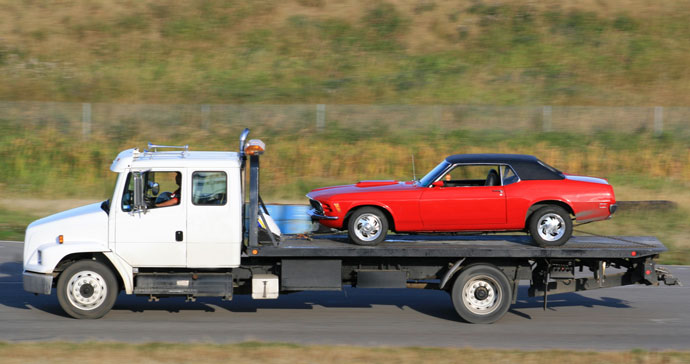 Vintage Red Ford Mustang getting transported on a flatbed trailer