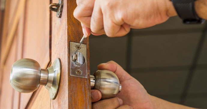 Locksmith working on a door dead bolt