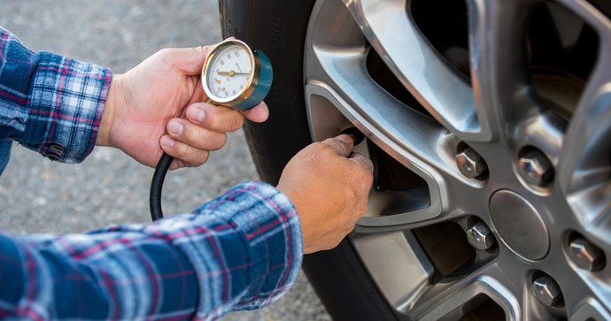 man checking his tire pressure