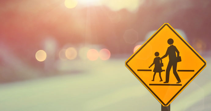 yellow crosswalk sign with blurred background