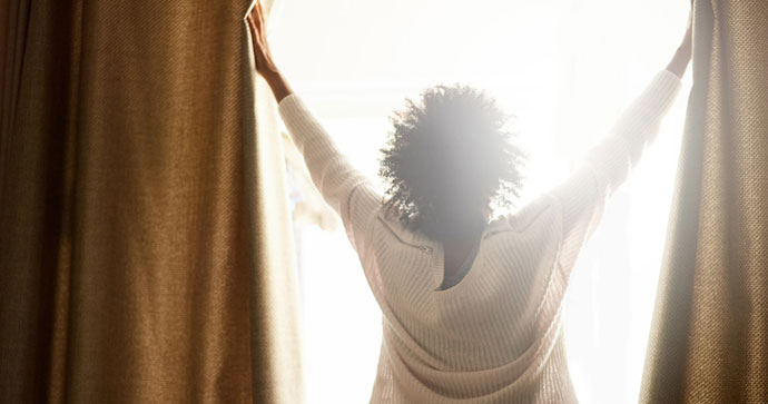 Woman opening up the drapes on a sunny day
