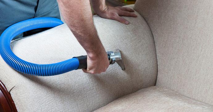 Man steam-cleaning a sofa