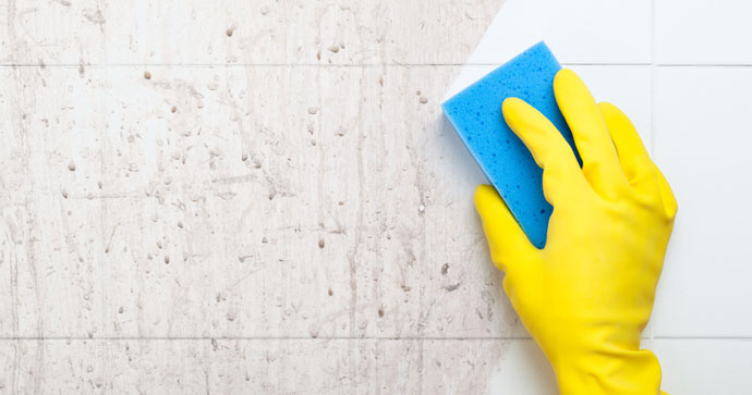 Hand in a rubber glove wiping away shower grime