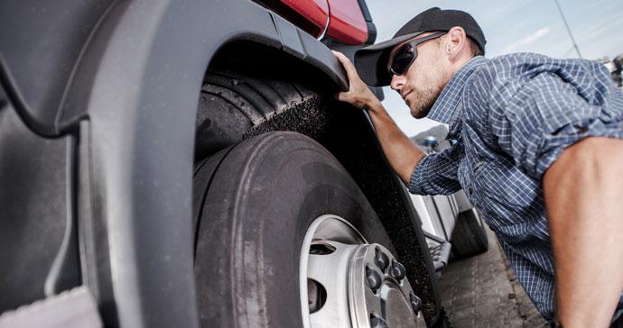 man inspecting truck wheel well