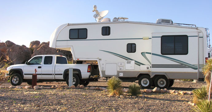 fifth wheel trailer attached to pickup truck in the desert